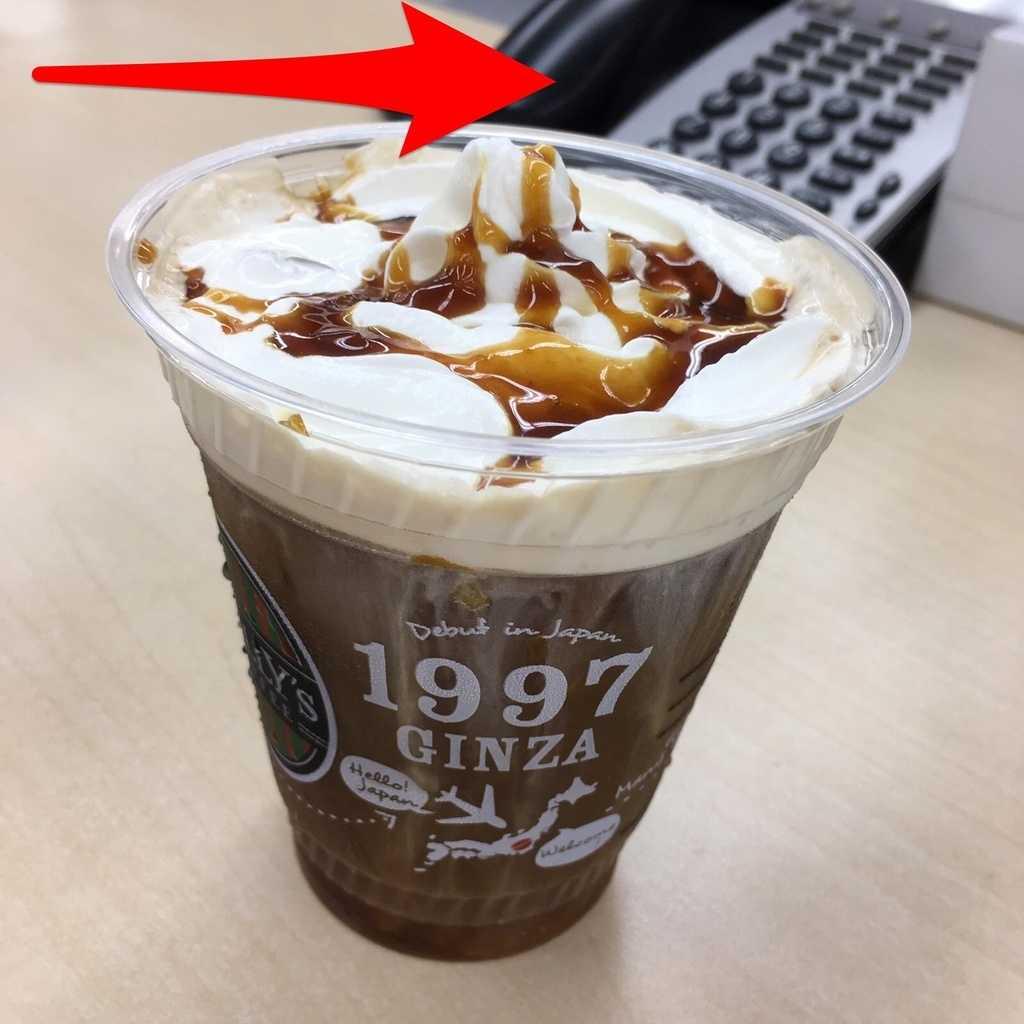 コーヒーの背後に映る電話で仕事してますアピール
